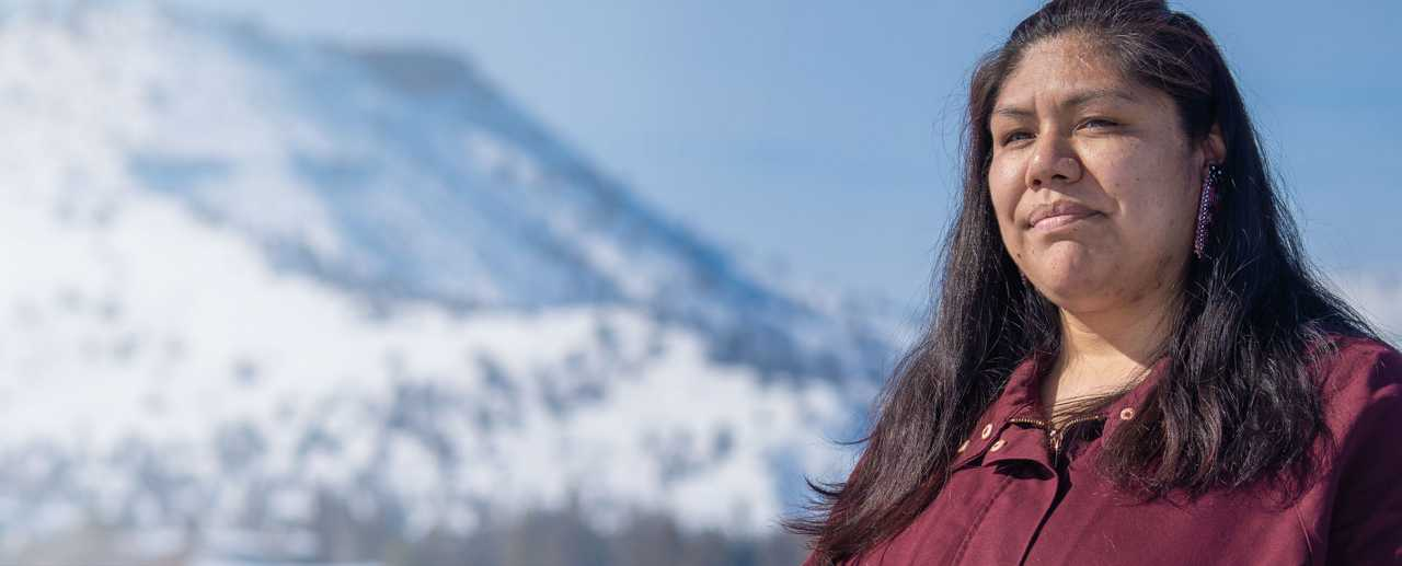 Woman standing in snow in front of mountain
