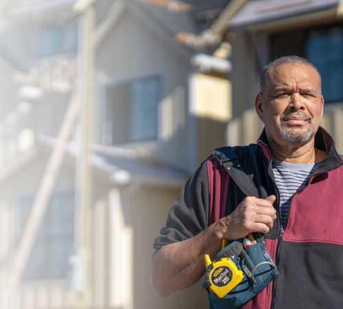 Man facing camera holding tool belt