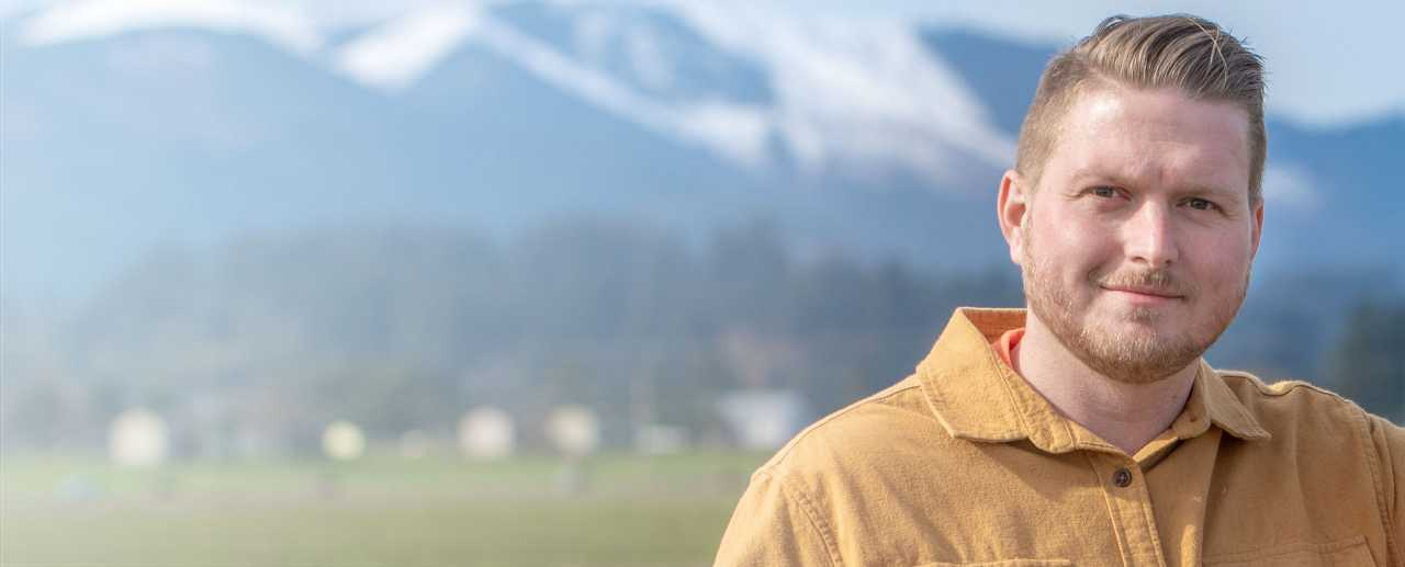 Man standing in field with mountains in background